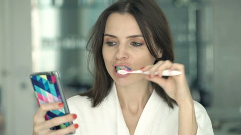 Young woman with smartphone brushing her teeth in bathroom