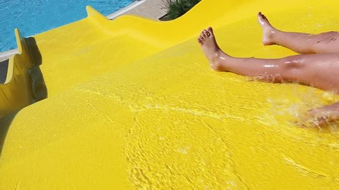 Child cheerfully slides down yellow waterslide in pool on sunny summer day. Real time full hd video footage.