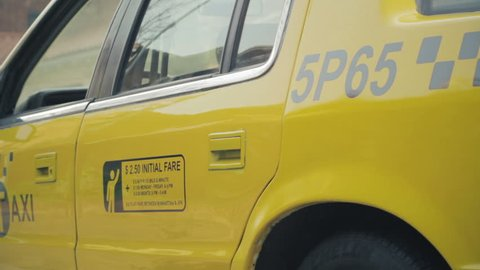 Door of a NYC Yellow taxi cab opening and closing. Yellow taxicabs can pick up passengers anywhere in New York