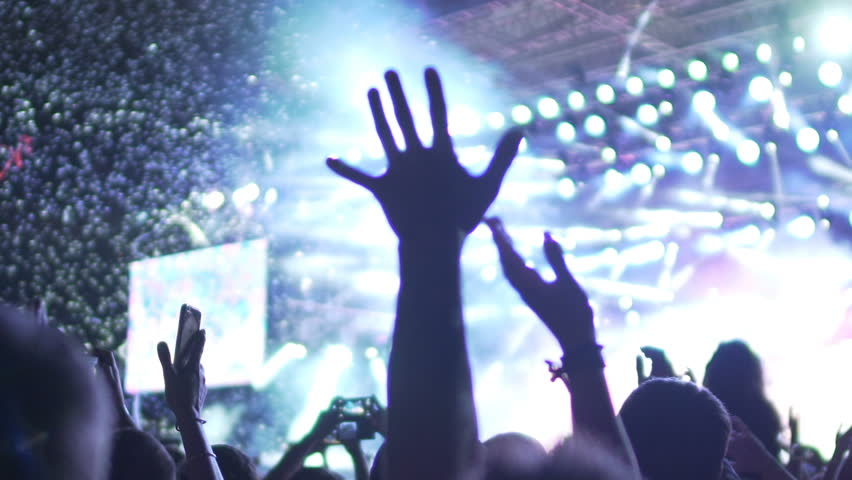 Crowd putting hands up in air at music concert, enjoying performance, slow-mo