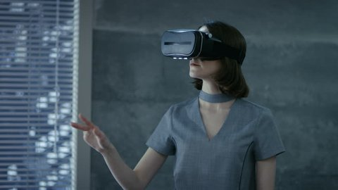 Stylish Young Woman Uses Virtual Reality Headset. She's chief IT Engineer for a New Promising Software Company.  Shot on RED EPIC-W 8K Helium Cinema Camera.