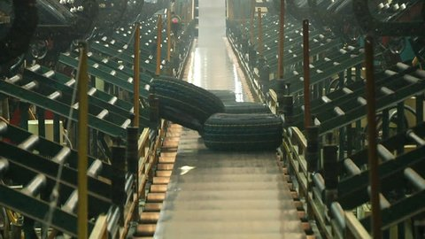 Smoked tires falls on conveyor belt from curing presses at the tires production plant