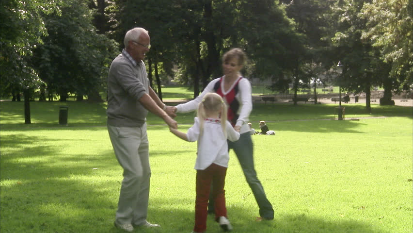Senior man, woman and child dancing in a park