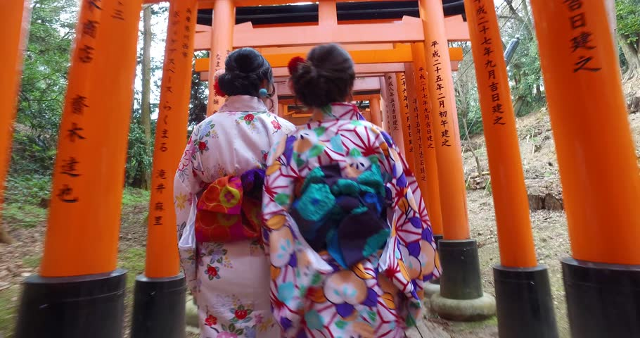 POINT OF VIEW: Women wearing traditional kimono walking inside Fushimi Inari Shrine. A Japanese monument, famous for its thousands of vermilion torii gates.