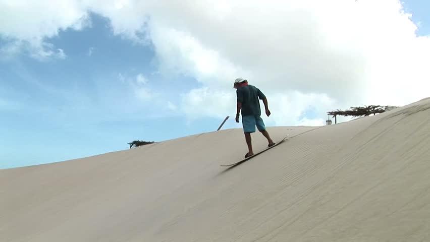 Man surfung on a sand in Jericoacoara, Brazil