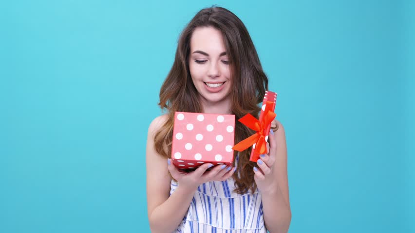 Young woman angry about bad gift and throwing it isolated