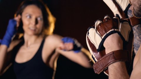 The close-up of the girl boxer hitting the focus mitts. 4K.