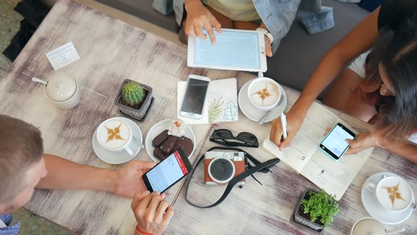 Hipster Friends Using Mobile Gadgets in the Coffee Shop.HD Slowmotion Lifestyle Closeup Hands and Table view from Above. Thailand. | Shutterstock HD Video #26502329