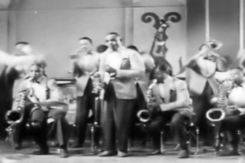 1940s: Jazz saxophone artist Erskine Hawkins and his orchestra play in the 1942 soundie.