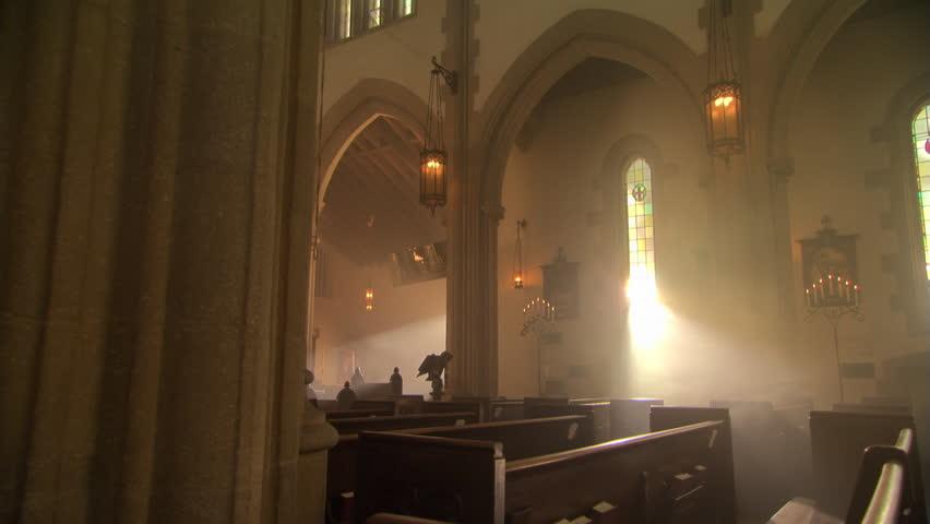 Sunbeams through stained glass windows in Catholic church, nun walking up aisle