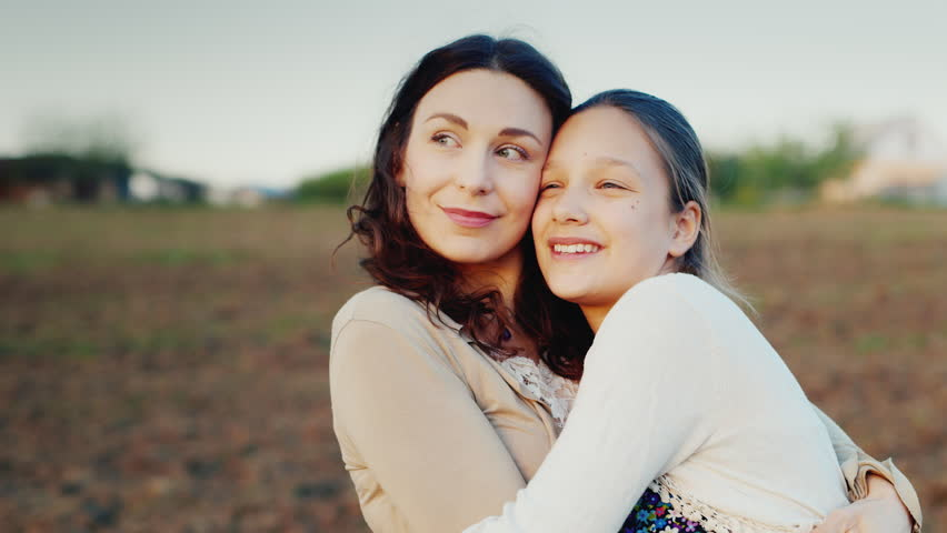 Mama gently hugs her daughter for 11 years. Together they look in one direction to the setting sun. Family values