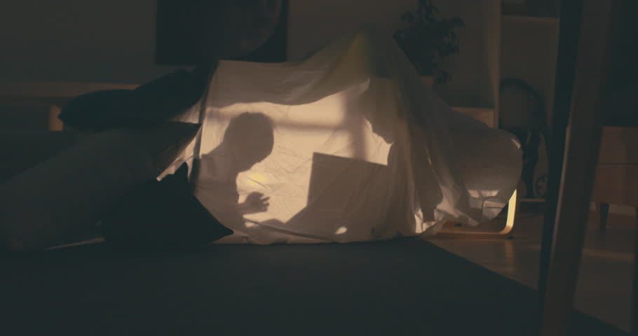 Silhouette of cute girl reading a book to her little brother inside a blanket fort in the evening, lit by a lamp from inside. 4K UHD RAW edited footage