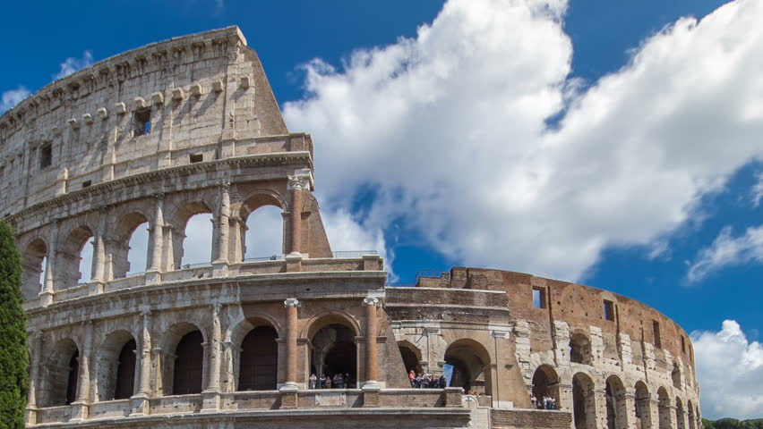 Many tourists visiting The Colosseum or Coliseum timelapse hyperlapse, also known as the Flavian Amphitheatre in Rome, Italy. Cloudy blue sky. Zoom out