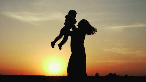 Happy child rushes into hands of mother. Family hugs over sunset sky background. Silhouettes of anonymous boy and woman outside in summer or autumn landscape. Slow motion 180fps