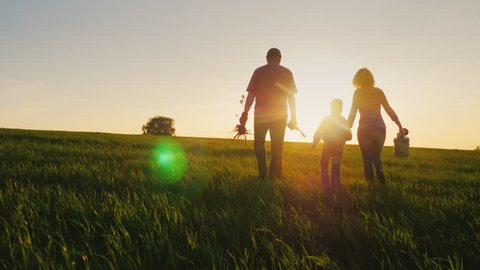 Rear view: A friendly family with a young son is going to plant a tree. Carry a seedling, shovel and watering can. Silhouettes in a beautiful field on a sunset background