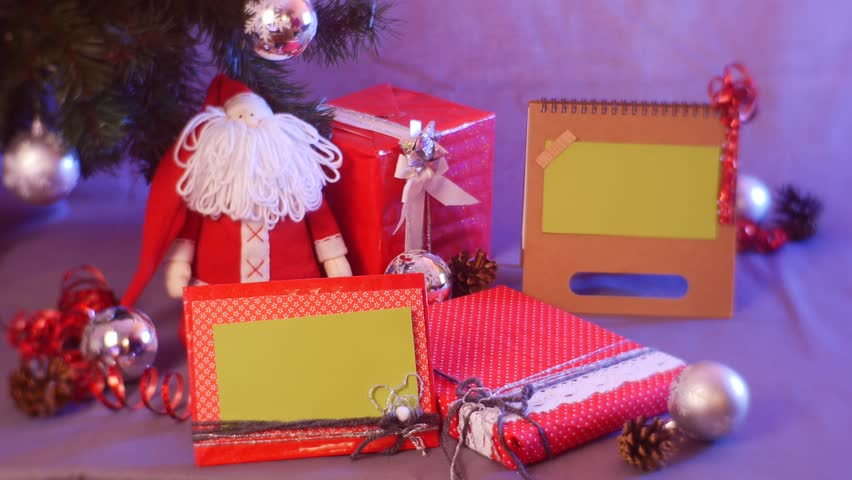Ready Festive Christmas Beautiful Composition of Gifts of Toys of Santa, Deer and Photo Frames, Where Women's Hands in a Red Sweater Put a Box With a Gift.new Year's Time For Family and Gifts, | Shutterstock HD Video #26559926