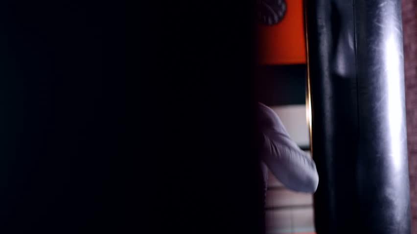 Close-up portrait. MMA fighter training in dark. 4K.
