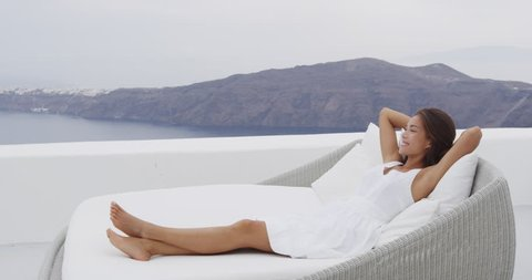Asian woman relaxing in sunbed at luxury apartment terrace outdoors on with incredible view of Caldera on Santorini, Greece, Europa. RED EPIC SLOW MOTION.