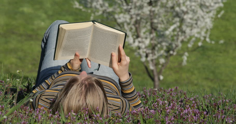 4K Female woman read book text lying on pasture, cherry tree in spring day in park