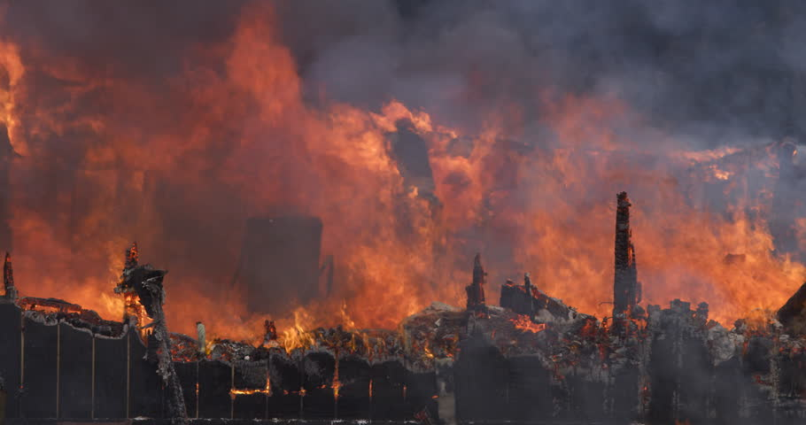 Flaming debris falls from a wall consumed by a raging house fire