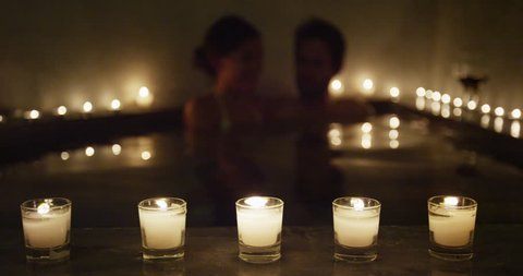 Young couple relaxing in romantic candlelit hot tub jacuzzi spa resort at night in private hotel room terrace. Romantic honeymoon getaway travel vacation adults enjoying their holidays.