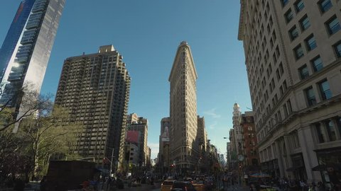 New York, USA - April 18 2017: Flatiron Building day view facade in Manhattan. External view of the Fuller Building, a 22-story triangular skyscraper on a busy day with traffic at 5th Avenue.