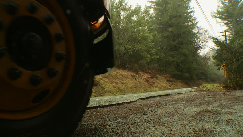 A school bus pulls away from a stop on a rural country road.