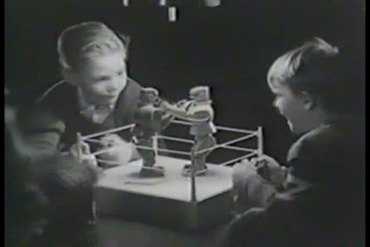 1960s: A television commercial for Rock 'Em Sock 'Em Robots, a two-player action toy, shows the mechanical boxers boxing, in 1964.
