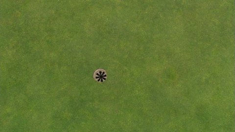 Overhead shot of hole on green and golf ball going in