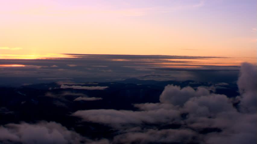 Evening flight over sparse cloud layer above mountainous terrain, passenger  POV