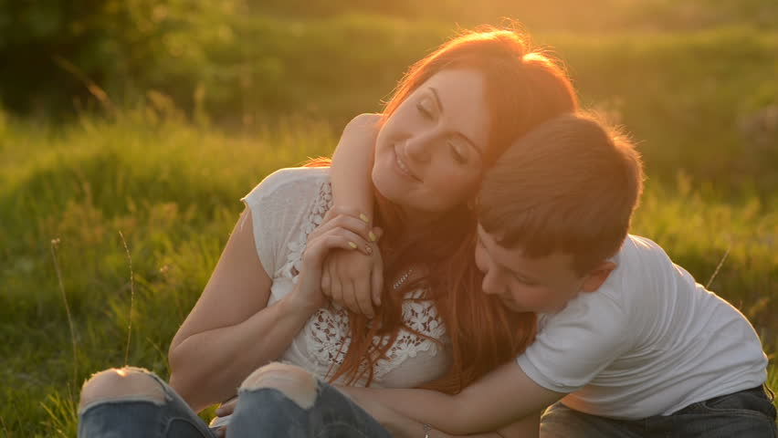 Young red-haired mother and her son having fun outdoors sitting on the grass, close-up #26636716