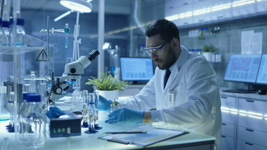 In a Modern Laboratory Research Scientist Conducts Experiments with Organic Materials. He Uses Pipette to Drop Fertilizers into Test Tube with Plant in it.  Shot on RED EPIC-W 8K Helium Cinema Camera. | Shutterstock HD Video #26643406