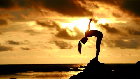 Long hair, good shape Asian woman playing yoga, exercise on rock at twilight light of evening at tropical beach with sunset and reflection of sun in the sea.