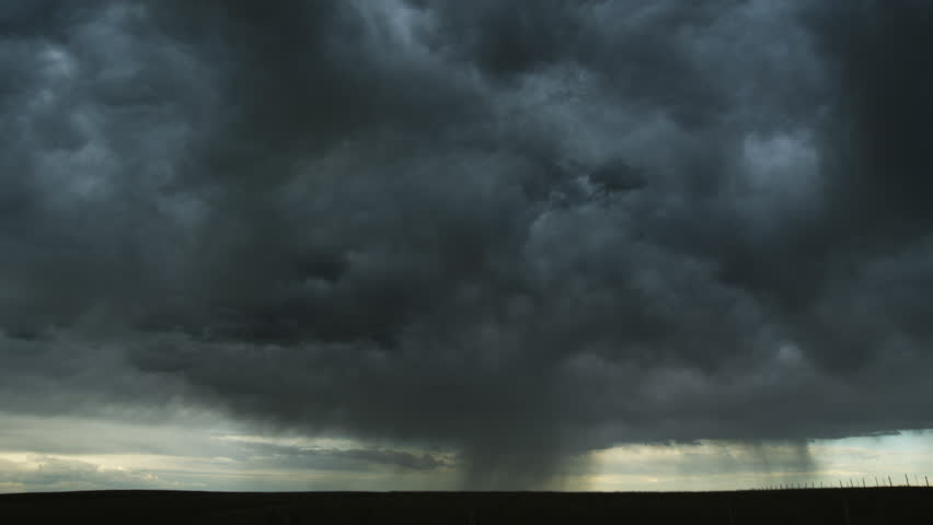 Massed gray clouds spilling rain roll away across the prairie, time lapse