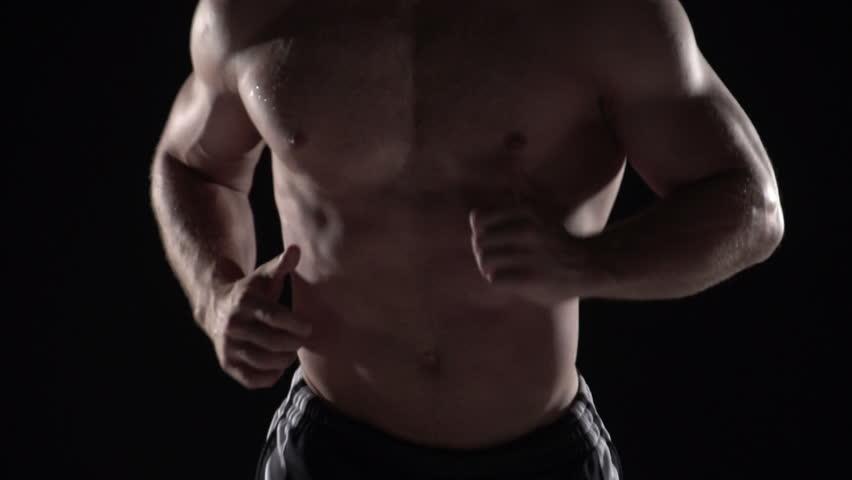 Muscular man running towards camera, torso shot center