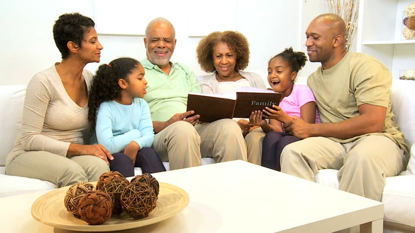 Three generations ethnic family relaxing home together looking photograph album