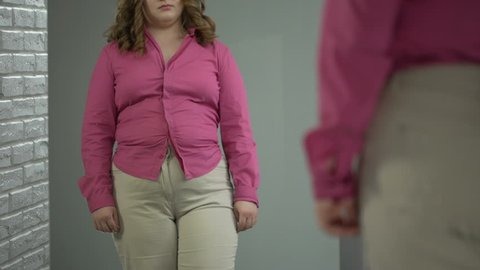 Lady buttoning up her shirt on stomach with great effort, obesity health problem
