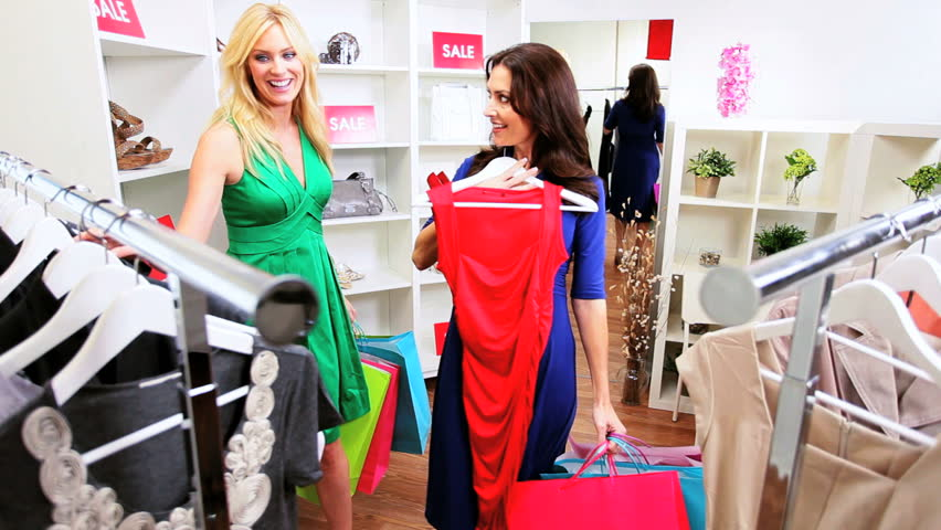 Mother And Little Daughter Shopping For Girls Clothes In A ...
