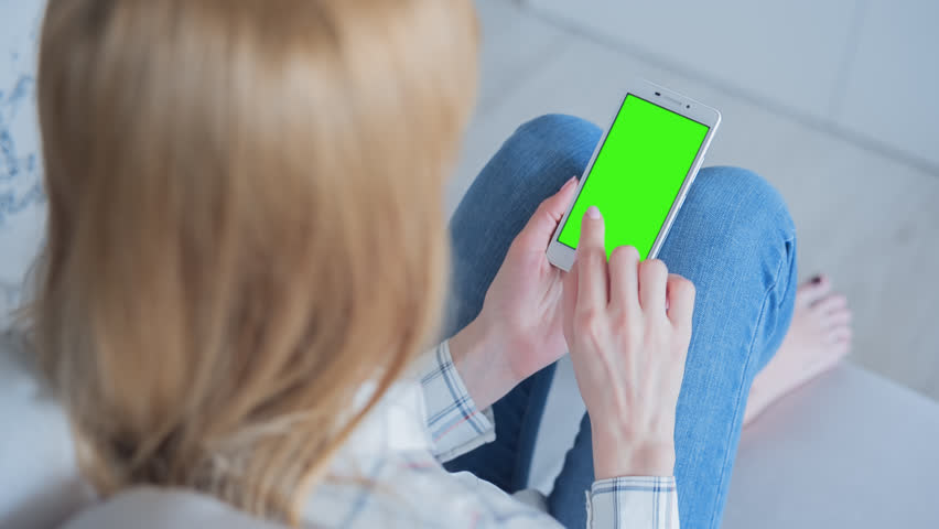 Young Woman sitting on a couch uses SmartPhone with pre-keyed green screen. Few types of motion - scrolling up and down, tapping, zoom in and out. Perfect for screen compositing. 10bit ProRes 444   Shutterstock HD Video #26707369
