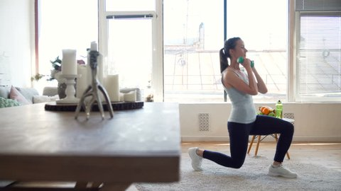 young fit and energetic woman doing sport workout and fitness lunge exercises with weights for healthy lifestyle in living room at home during sunny day