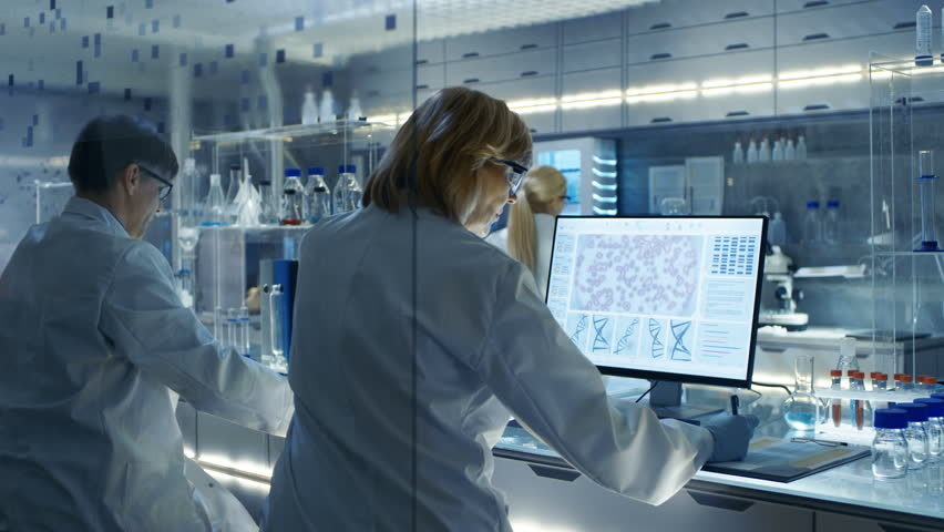 Female and Male Scientists Working on their Computers In Big Modern Laboratory. Various Shelves with Beakers, Chemicals and Different Technical Equipment is Visible.Shot on RED EPIC-W 8K Helium Camera