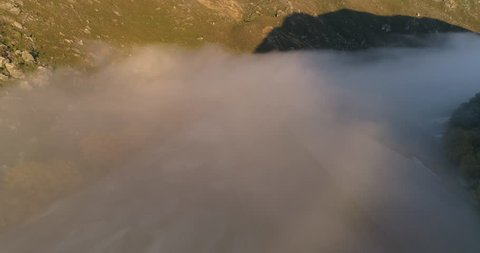 Aerial footage in New Zealand, in autumn. The blanket of clouds rush out over the river.