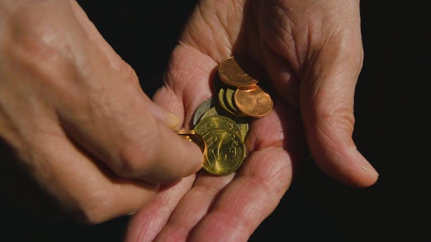 Elderly Man Counts Euro Coins In Hand