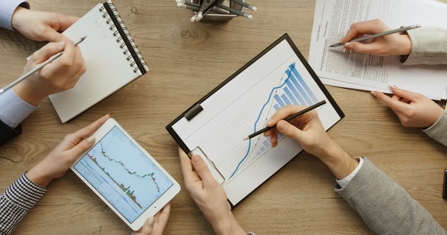 Hands top view. Business. Team working together at office desk, man is working with tablet and checking financial reports and woman are writing, noting information in notebook. Slow motion.  | Shutterstock HD Video #26737096
