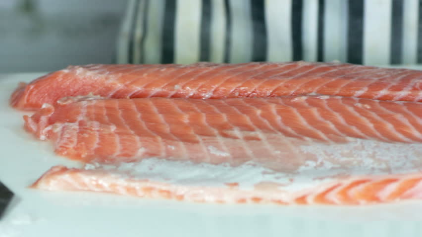 Cooking. Chef cutting the salmon, preparing salmon for sushi, cutting fish by knife, Slicing salmon fillets | Shutterstock HD Video #26750026