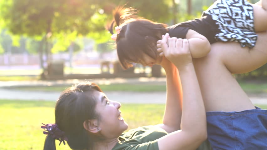 Asian mom play with her daughter at nature park. relex  | Shutterstock HD Video #26753806