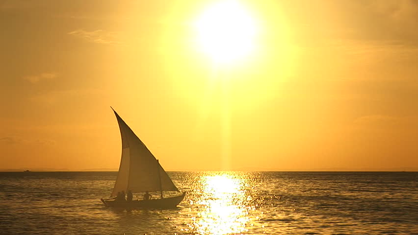 Boat in front of a big sun at Salvador, Bahia, Brazil
