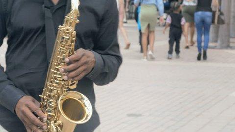 Musician playing saxophone on city sidewalk closeup