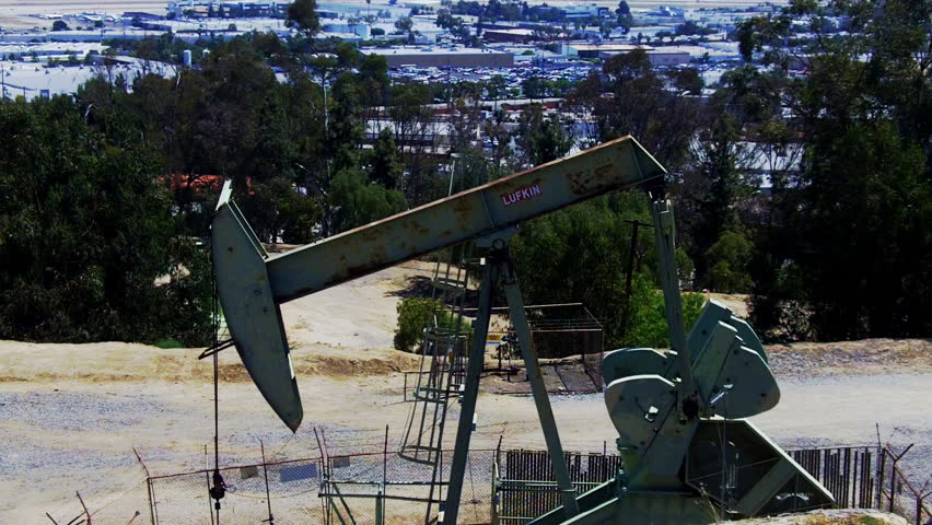 An oil well pumping rig in the foreground and an urban Los Angeles landscape