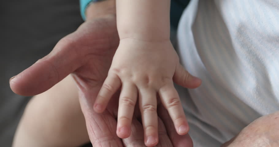 Old wrinkled hands touching the baby's soft hands. Close-up of the hands of the kid and grandmother. 4K. | Shutterstock HD Video #26802442